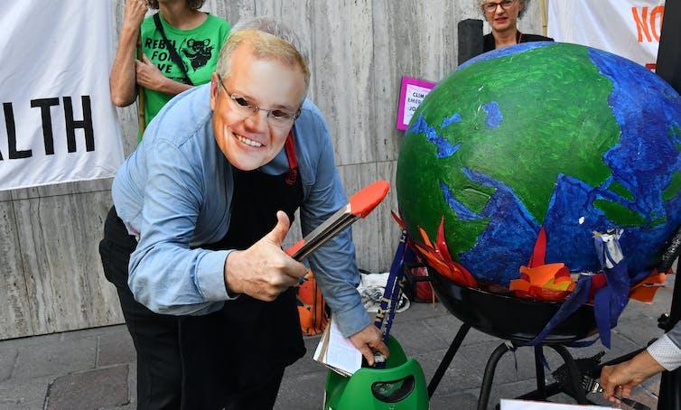 Person in Scott Morrison mask leans over burning globe, holding tongs