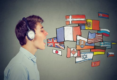 Young man speaks with eyes closed and headphones on, as cartoon flags come out of his mouth.