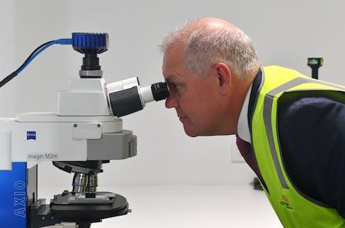 Scott Morrison, looking into a microscope