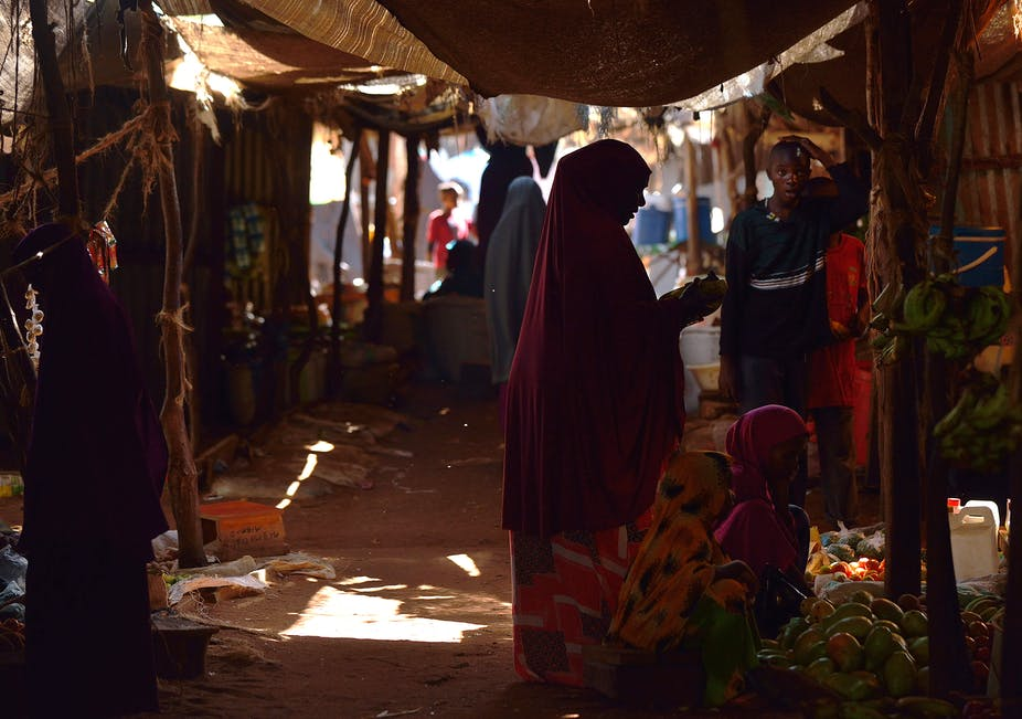 A woman in a flowing red cover-all shops for fruits and vegetables at a market