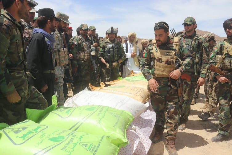 Afghani soldiers looking at bags of ammonium nitrate.