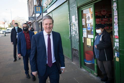 Keir Starmer walking past a shop as a person wearing a mask looks on.