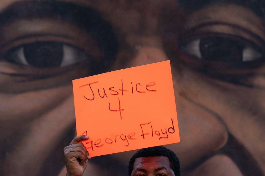 Un homme brandit une pancarte devant une fresque représentant George Floyd après l'annonce de la la reconnaissance de la culpabilité de Derek Chauvin, le 20 avril 2021, à Atlanta