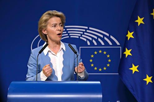 Ursula von der Leyen speaking in front of an EU flag