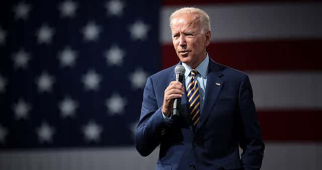 President Biden speaking with a microphone in front of an American flag.