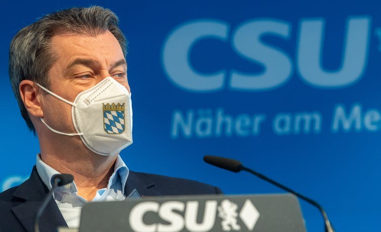 Bavarian State Premier Markus Soeder attends a press conference wearing a facemask decorated with the Bavarian coat of arms.
