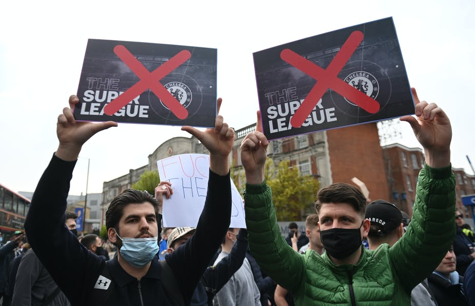 Two men wearing face masks in protest crowd hold up European Super Leaue posters with red crosses over both of them
