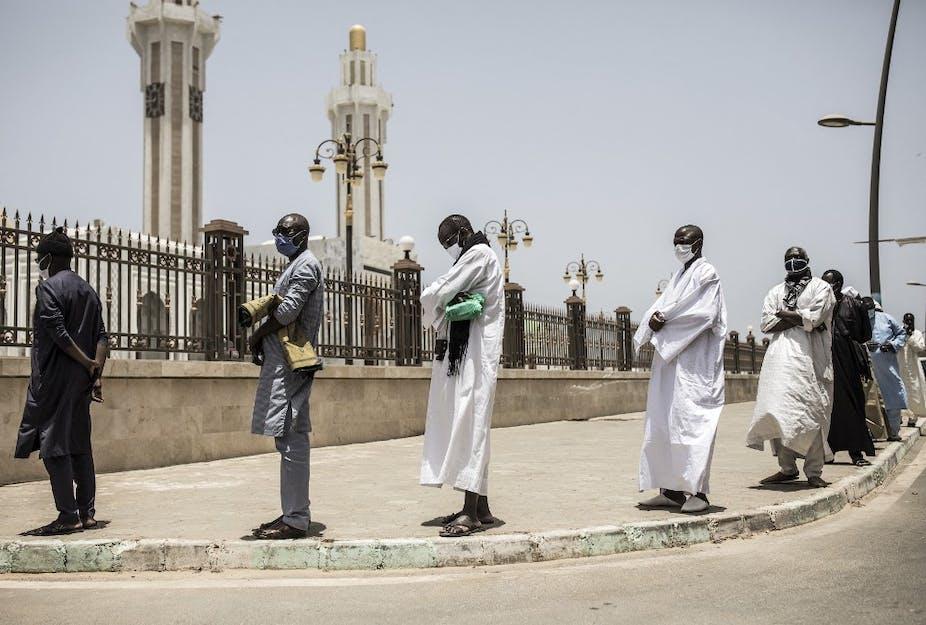 Des fidèles font la queue pour se laver les mains avant la prière du vendredi à la mosquée des Mourides, qui ouvre pour ses premières prières du vendredi après deux mois à Dakar, le 15 mai 2020.