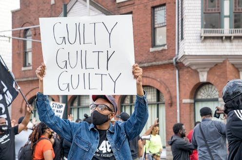 """A person in a crowd holding a sign that says, """"GUILTY GUILTY GUILTY"""""""