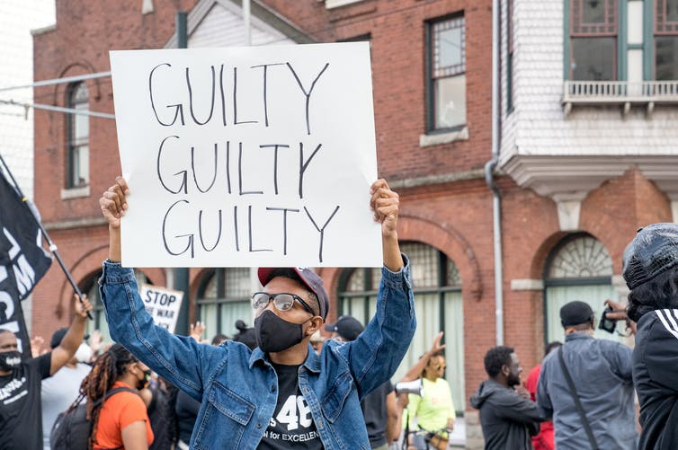 person holding sign reading guilty guilty guilty
