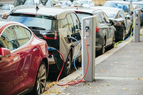 Coches eléctricos aparcados y recargando baterías.