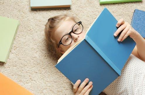 Una niña con gafas leyendo tumbada un libro de tapas azules.
