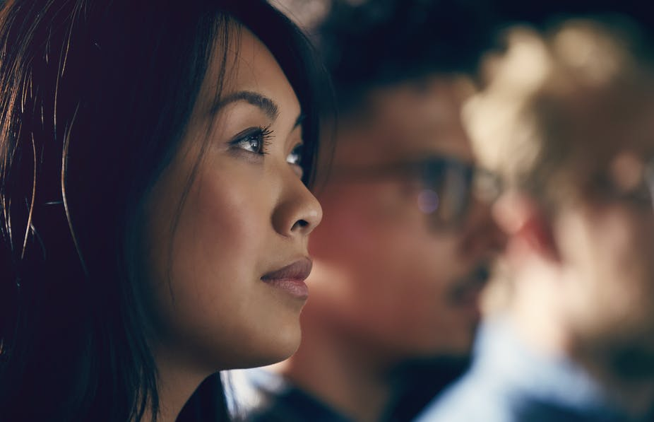 A young Asian American woman watches a presentation.