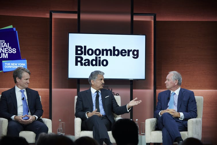 Three CEOs sit on comfy chairs in front of a Bloomberg Radio sign on a screen.