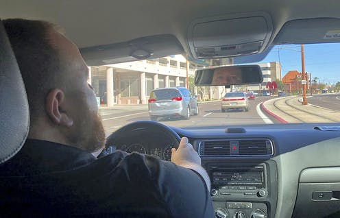 An Uber driver looks in the rear view mirror as he drives on a road near the Phoenix airport.