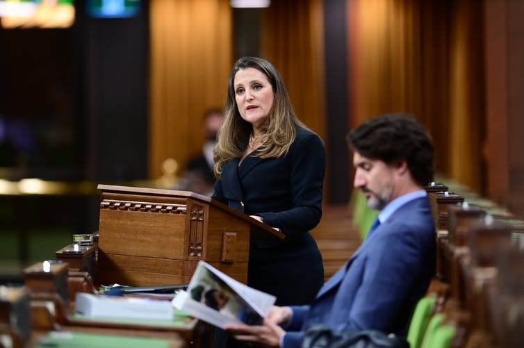 Freeland delivers the budget as Trudeau sits beside her reading the document.