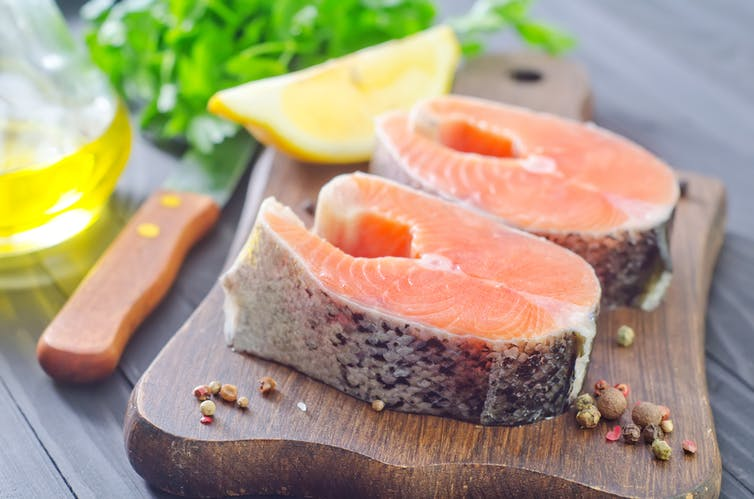 Two pieces of salmon with lemon wedge