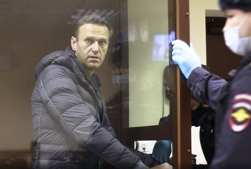 Alexei Navalny stands in a cage during a court hearing in February.