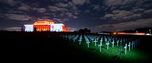 War Memorial Museum with poppies projected on walls and white crosses on front lawn