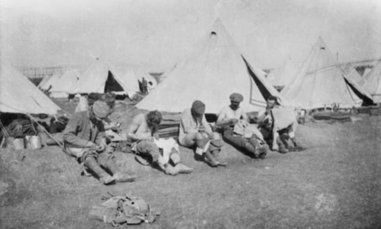 Soldiers delousing clothing outside tents