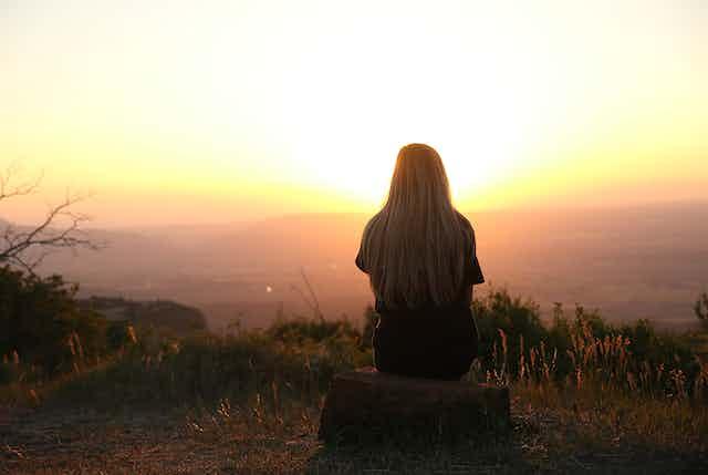 Woman sitting alone watching sunset.