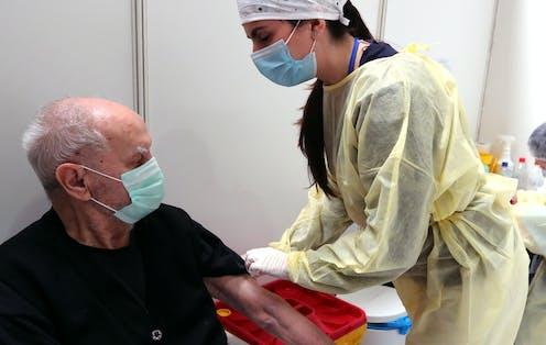 A nurse administering a dose of the AstraZeneca vaccine to a man