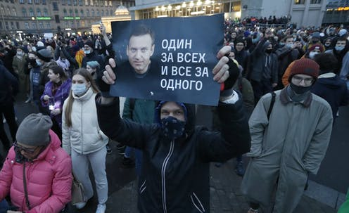 A protester in St Petersburg, Russia holds up a banner with a picture of dissident leader Alexei Navalny. In the background are thousands of other demonstrators.