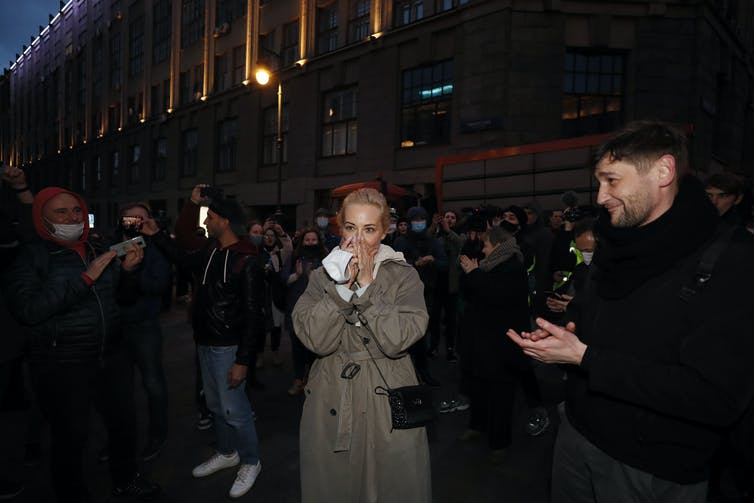 Yulia Navalnaya, wife of the Russian jailed opposition leader Alexei Navalny, covers her mouth as fellow protesters applaud.