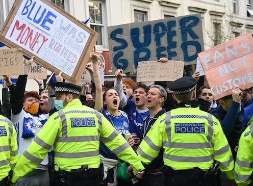 Protesting football fans held back by a line of police.