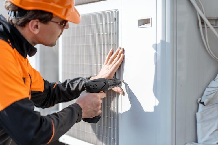 An engineer installing a heat pump.