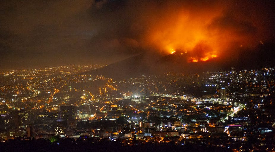 A raging fire at night time burning on the mountain. Below is the brightly lit city.
