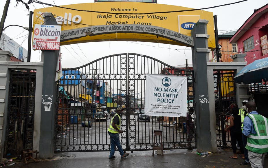 Men wearing reflective jackets standing at the main gate of Computer Village, Lagos.