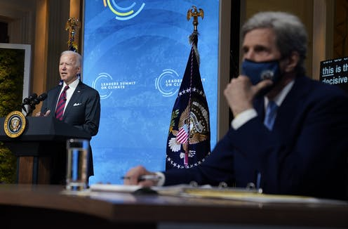 Biden speaking to the camera and Kerry, wearing a face mask, sitting to the side.