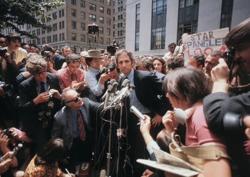 Ellsberg stands in front of microphones surrounded by reporters and photographers.