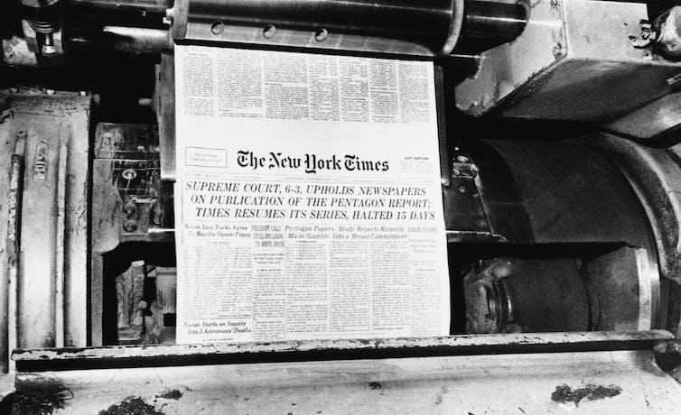 Una imprenta escupe una copia de un periódico.