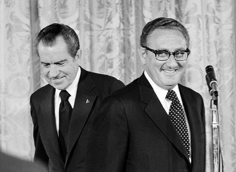 Henry Kissinger se para ante un micrófono frente a Richard Nixon.