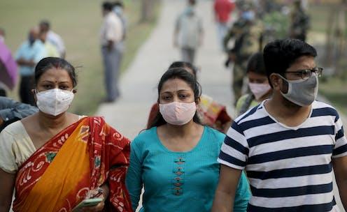 People in India walking outside wearing masks