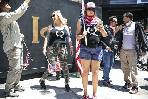 A group of protesters, including two women with QAnon emblems on their t-shirts, rallying against pandemic restrictions in California.