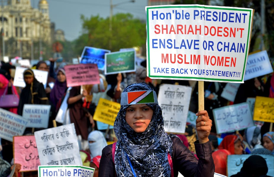 Indian women holding placards saying, 'Sharia does not enslave or chain Muslim women,' during a protest in Kolkata, India.