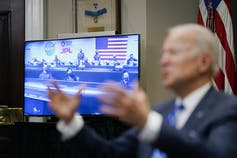 Biden gestures with footage of the Mars Perseverance team on a screen behind him.