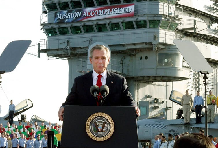 George W. Bush stands in front of a podium on an aircraft carrier with a banner behind him declaring Mission Accomplished.