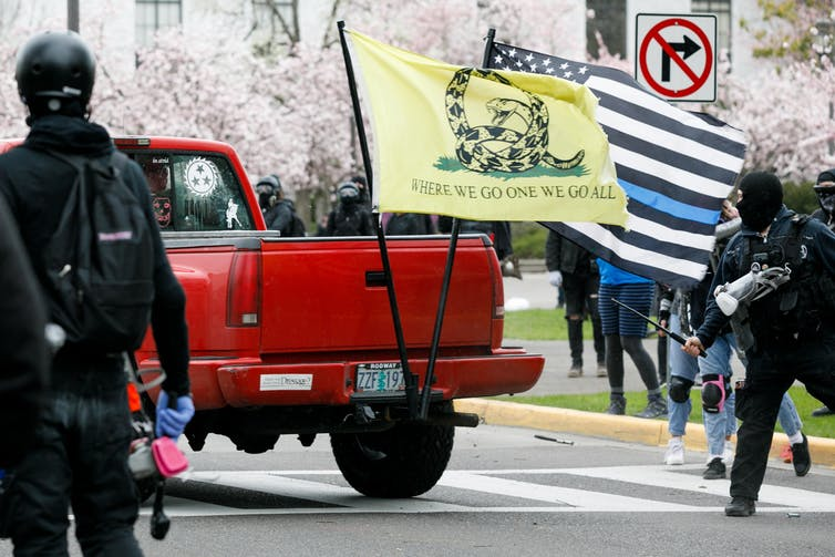 A truck bearing a QAnon flag is chased by anti-fascist counterprotesters down a street in front of the Oregon state capitol building.