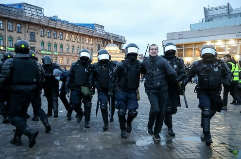Police in riot gear walk a man in handcuffs through a public square