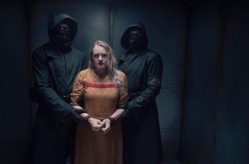 Production image: June held by two figures in black.