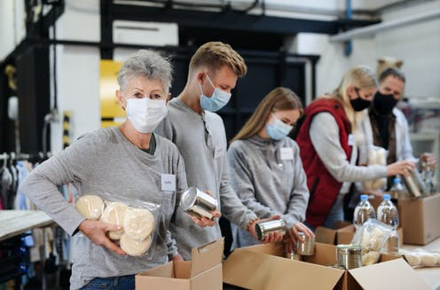 Masked volunteers sort charity donations in a food bank