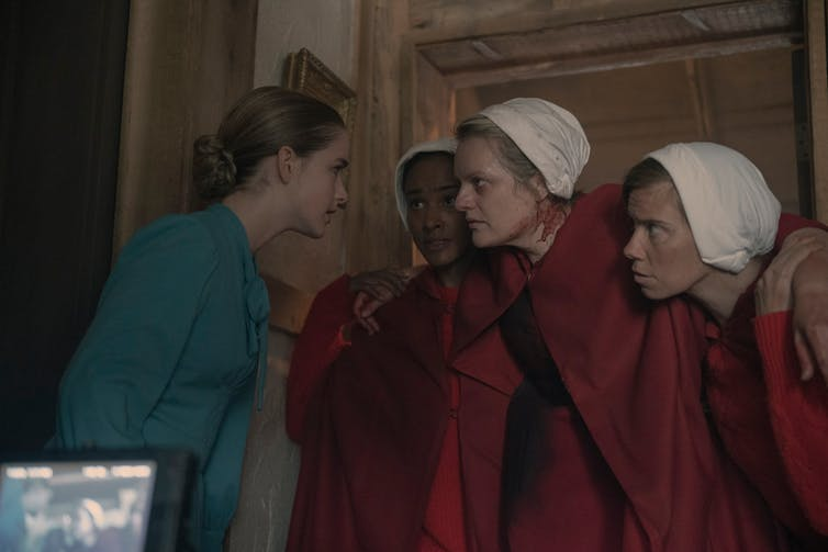 Serena in blue; three handmaids in red.