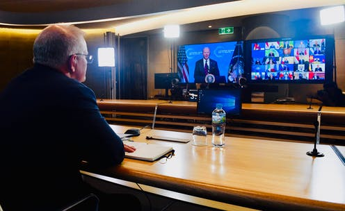 Scott Morrison in front of screens featuring Joe Biden and other leaders