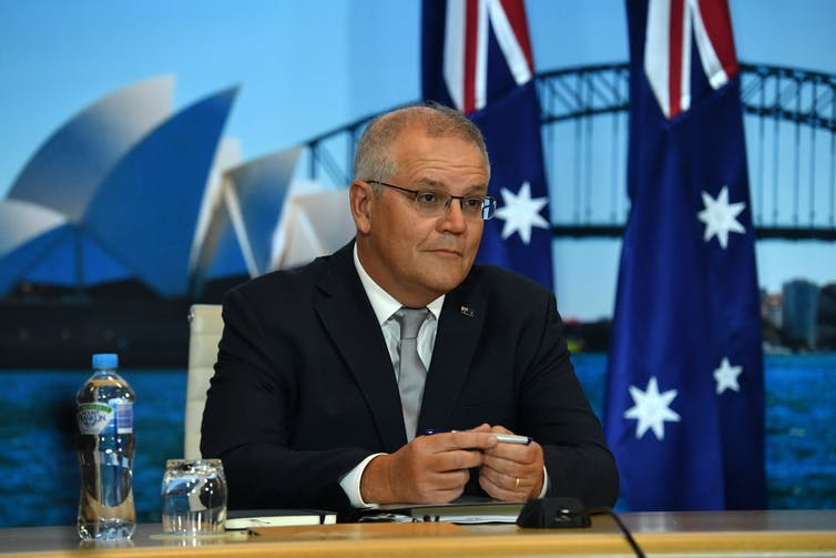 Scott Morrison in front of Sydney harbour backdrop and Australian flags