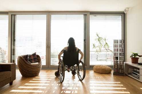 A woman sits in a wheelchair looking out the window.