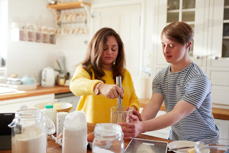 Two people with Down Syndrome cooking in the kitchen.